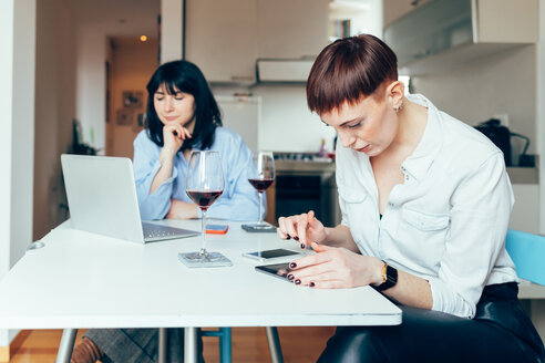 Women sitting at table using laptop and digital tablet - CUF45139