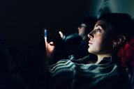 Women in bed in darkness using mobile phones - CUF45151