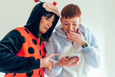 Women wearing adult bodysuits looking at mobile phone - CUF45154