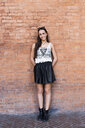 Portrait of fashionable young woman standing in front of brick wall - GIOF04663