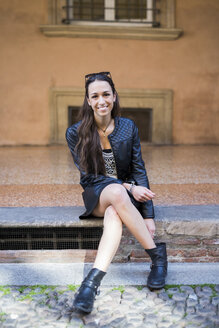 Portrait of fashionable young woman sitting on step - GIOF04666