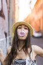 Portrait of young woman blowing bubble gum - GIOF04675