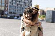 Portrait of happy young man giving his girlfriend a piggyback ride - GIOF04678