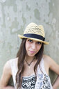 Portrait of smiling young woman wearing straw hat - GIOF04681