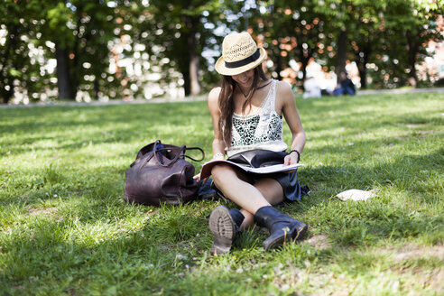 Smiling young student sitting on a meadow in a park using copybook - GIOF04687