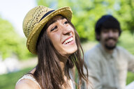 Portrait of happy young woman in a park with her boyfriend in the background - GIOF04693