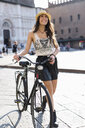 Italy, Bologna, portrait of fashionable young woman with bicycle in the city - GIOF04705