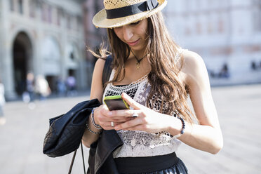 Italy, Bologna, young woman using smartphone - GIOF04708
