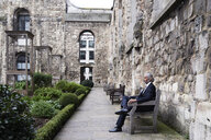 UK, London, senior businessman sitting on bench in a courtyard relaxing - IGGF00607