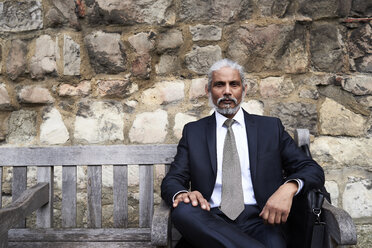 Portrait of senior businessman sitting on bench wearing suit and tie - IGGF00610