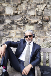 Portrait of senior businessman wearing suit and tie sitting on bench listening music with headphones - IGGF00613