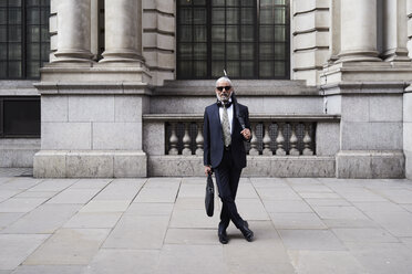 UK, London, portrait of stylish businessman with sunglasses and umbrella wearing suit and tie - IGGF00619