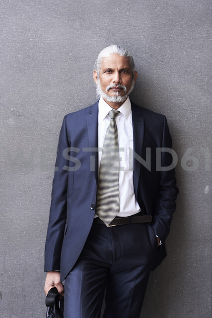 Portrait of senior businessman with grey hair and beard wearing suit and tie - IGGF00622