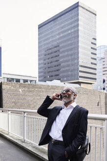 UK, London, laughing senior businessman on the phone outdoors - IGGF00631