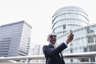 UK, London, grey-haired senior businessman pulling funny faces while taking selfie - IGGF00634