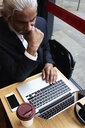 Senior businessman working on laptop in a coffee shop - IGGF00637