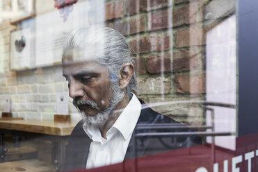 Senior businessman behind windowpane in a coffee shop - IGGF00640