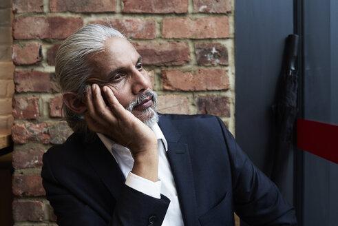 Portrait of daydreaming senior businessman in a coffee shop - IGGF00643