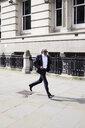 Senior businessman running on pavement in the morning - IGGF00646