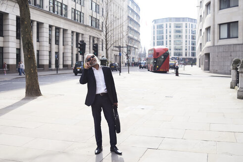 UK, London, laughing senior businessman on the phone in the city - IGGF00649