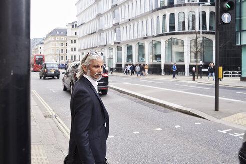 UK, London, senior businessman waiting at crosswalk in the morning - IGGF00658