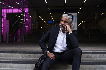 Stylish senior businessman sitting on stairs outdoors - IGGF00661