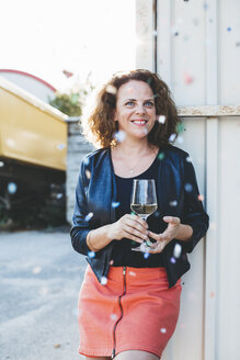 Portrait of smiling woman with glass of white wine looking at flying confetti - HMEF00015