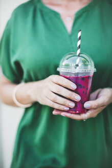 Woman's hands holding plastic cup of pink smoothie, close-up - HMEF00017