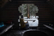 Finland, Kuopio, woman sitting in wooden hut in winter looking at campfire - PSIF00114