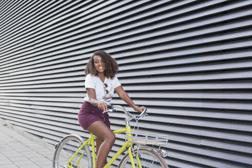 Portrait of smiling young woman riding bicycle - JUNF01473