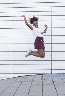 Portrait of laughing young woman jumping in the air - JUNF01479