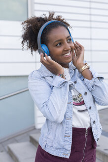 Portrait of smiling young woman listening music with headphones - JUNF01482