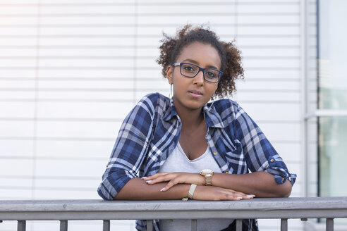 Portrait of young woman wearing glasses leaning on railing - JUNF01485