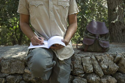 Man with backpack sitting on a wall in nature writing in notebook, partial view - JPTF00008