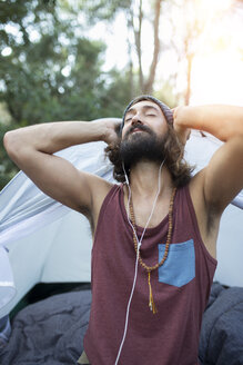 Portrait of man in front of tent listening music with earphones - JPTF00020