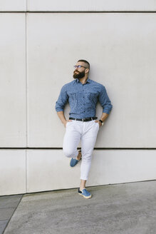 Bearded hipster businessman wearing glasses and plaid shirt leaning against wall - FMGF00011