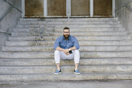 Portrait of bearded hipster businessman with smartphone sitting on stairs - FMGF00014