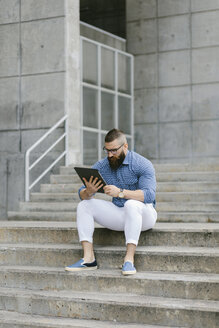 Bearded hipster businessman sitting on stairs using digital tablet - FMGF00023