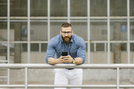 Portrait of bearded hipster businessman with smartphone  leaning on railing - FMGF00026