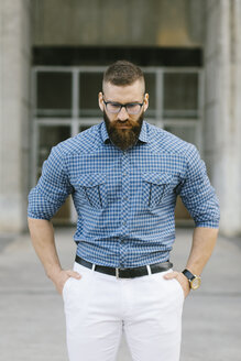 Portrait of bearded hipster businessman wearing glasses and plaid shirt - FMGF00032