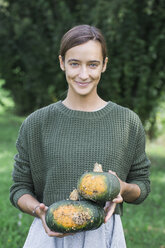 Porrtait of smiling young woman with two pumpkins in the garden - ALBF00612