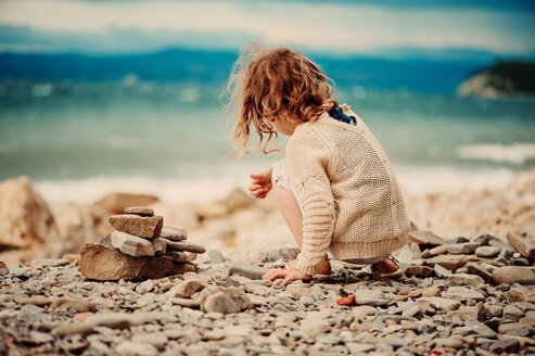 A young girl playing with stones on the beach in Slovenia - INGF00019