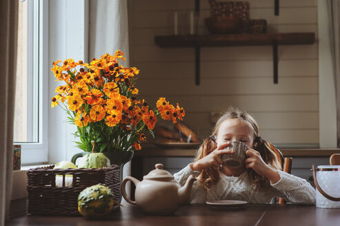 Portrait of a young girl sitting on a table full of bright flowers at home - INGF00037