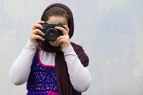 Portrait of a child photographing against a white wall - INGF00121