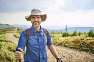 Portrait of smiling man hiking in the mountains - BSZF00668