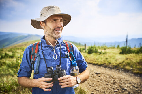 Smiling man with binoculars hiking in the mountains - BSZF00671