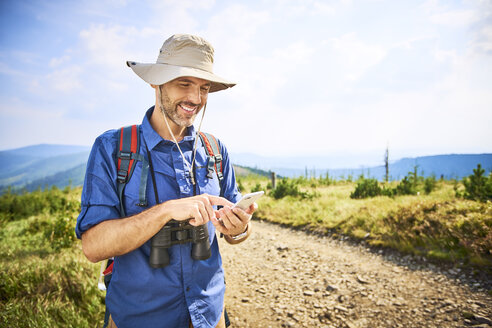 Smiling man checking his cell phone during hiking trip - BSZF00677