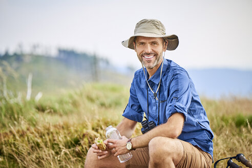 Portrait of smiling man resting and eating sandwich during hiking trip - BSZF00680