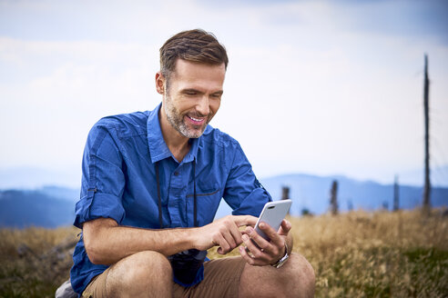 Smiling man resting and checking his cell phone during hiking trip - BSZF00683
