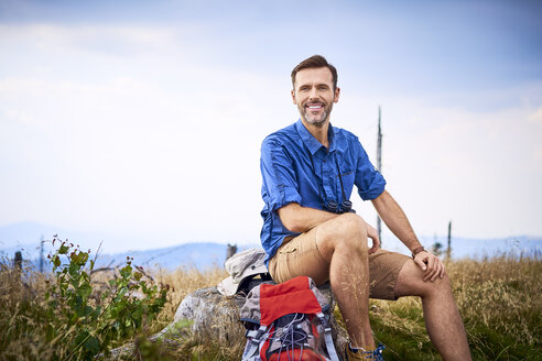 Portrait of smiling man resting during hiking trip - BSZF00686